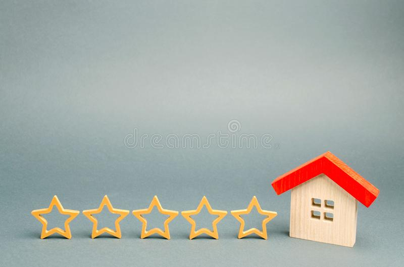 Cinq ?toiles et une maison en bois sur un fond gris Le concept du meilleur logement, classe de luxe des appartements VIP Le meill photographie stock libre de droits