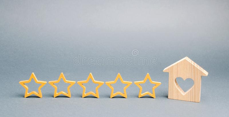 Cinq ?toiles et une maison en bois sur un fond gris Le concept du meilleur logement, classe de luxe des appartements VIP Le meill photos stock