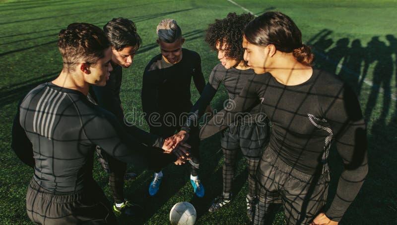 Cinq une équipe de football latérale remontant leurs mains image stock