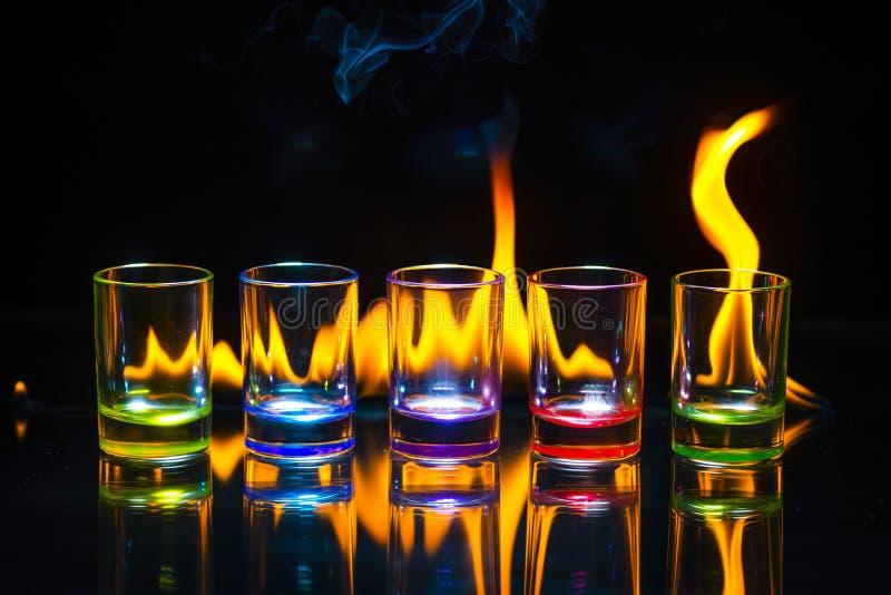 Cinq verres à liqueur vides multicolores ont réfléchi sur le ressac en verre photos libres de droits