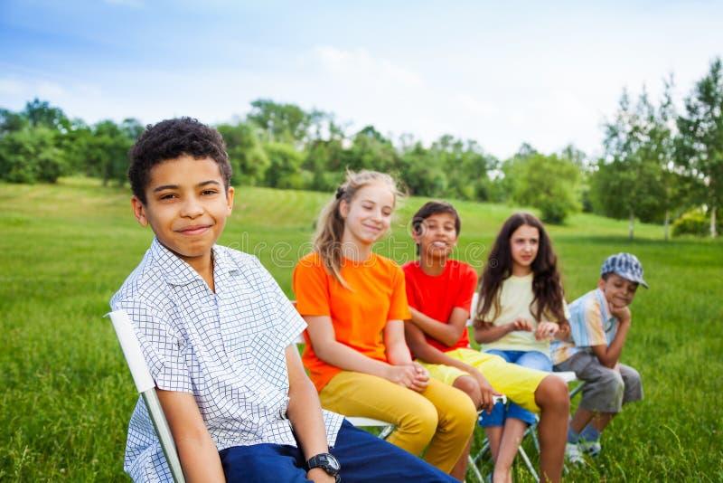 Cinque amici felici si siedono sulle sedie nella fila all'aperto fotografia stock