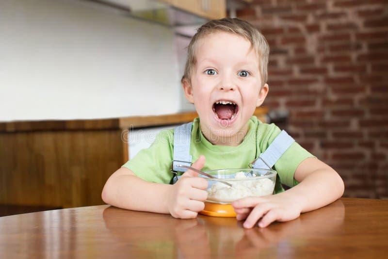 Cinque anni di ragazzo hanno aperto la sua cucina del porridge della bocca fotografie stock libere da diritti