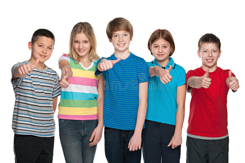 Cinque bambini felici tengono i suoi pollici su immagine stock