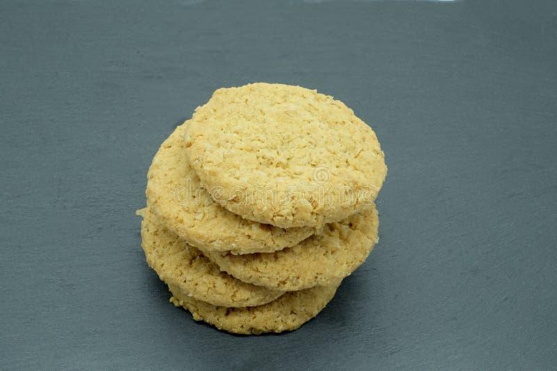 Cinque biscotti della farina d'avena in un mucchio su un piatto Slated nero immagini stock libere da diritti