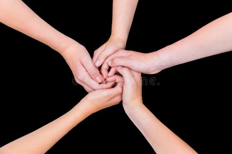 Cinque braccia adolescenti con le mani impigliate isolate sul backgro nero fotografia stock libera da diritti