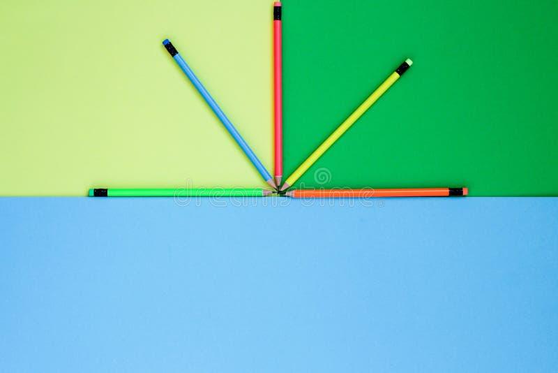 Cinque colori al neon delle matite si trovano su un fondo colorato come un fan fotografia stock libera da diritti