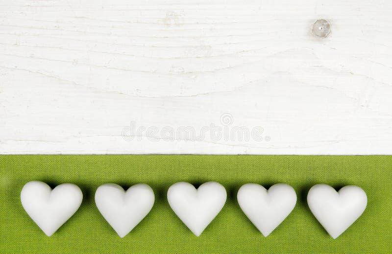 Cinque cuori bianchi su fondo elegante misero bianco di legno con il ap immagine stock libera da diritti