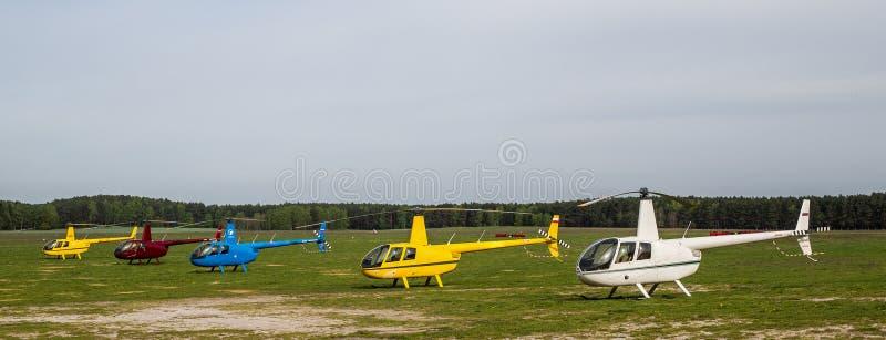 Cinque elicotteri multicolori sul campo di decollo immagini stock libere da diritti