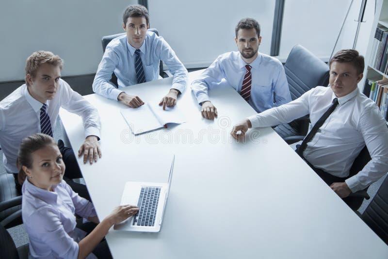 Cinque genti di affari che hanno una riunione d'affari alla tavola nell'ufficio, esaminante macchina fotografica fotografia stock