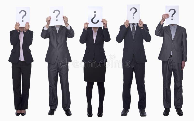 Cinque genti di affari che sostengono carta con il punto interrogativo, fronte oscurato, colpo dello studio fotografie stock libere da diritti