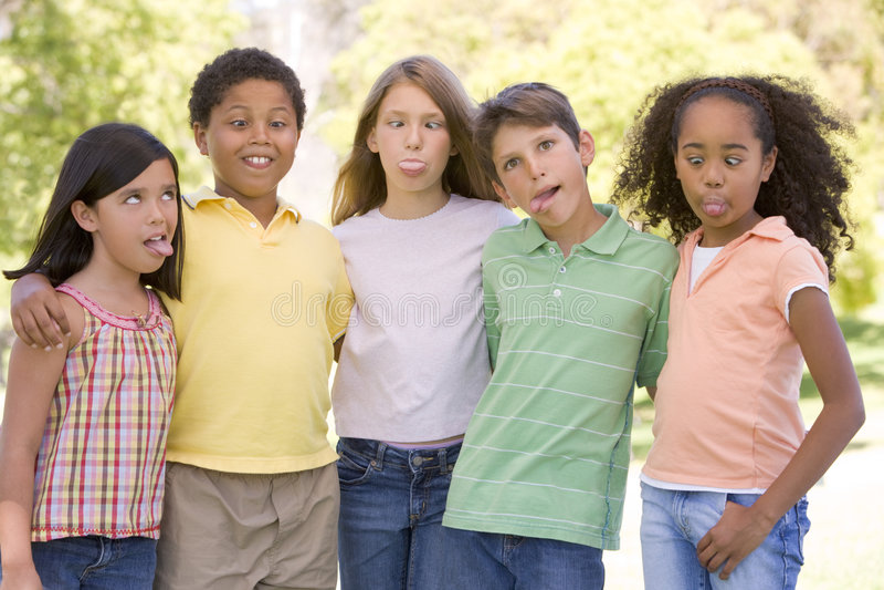 Cinque giovani amici all'aperto che fanno i fronti divertenti immagini stock