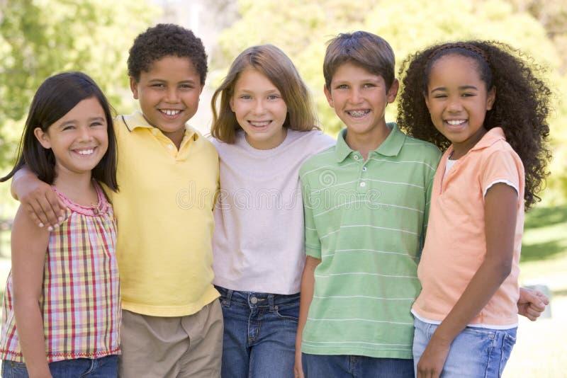 Cinque giovani amici che si levano in piedi all'aperto sorridenti fotografie stock libere da diritti