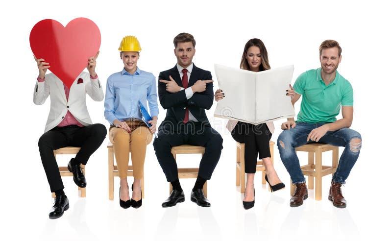 Cinque giovani divertendosi aspettando un'intervista di lavoro fotografia stock