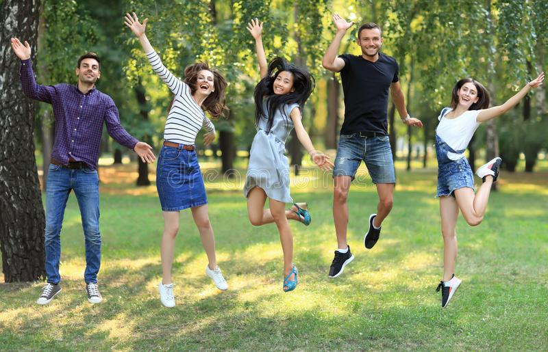 Cinque giovani donne ed uomini felici degli amici che saltano all'aperto fotografie stock libere da diritti