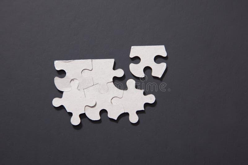 Cinque insieme pezzi di puzzle eccetto uno immagine stock