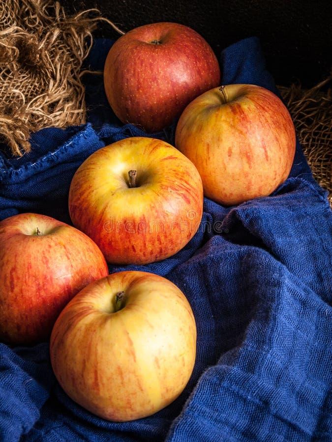 Cinque mele su un fondo rustico di legno semplice, con un panno strutturato blu fotografia stock