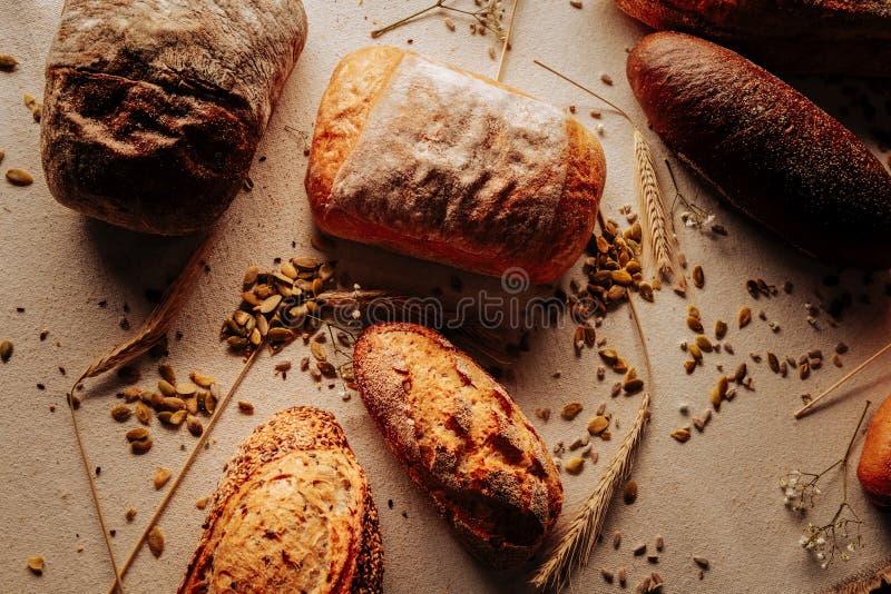 Cinque pagnotte del pane di segale e del grano che si trova sulla tavola in forno immagini stock libere da diritti