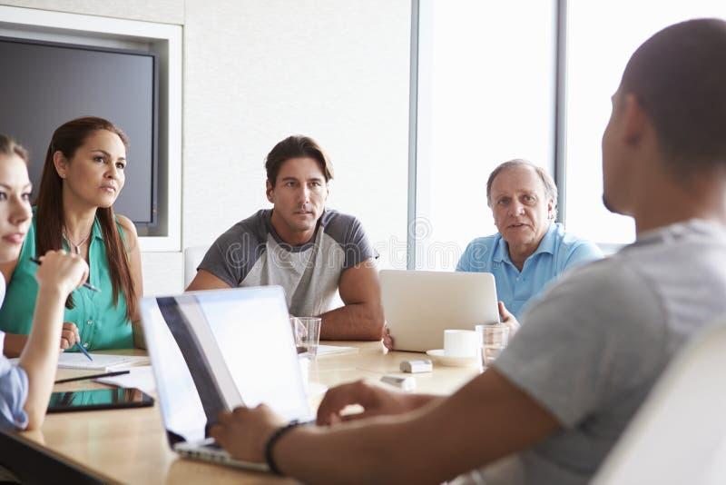 Cinque persone di affari che hanno riunione in sala del consiglio fotografie stock