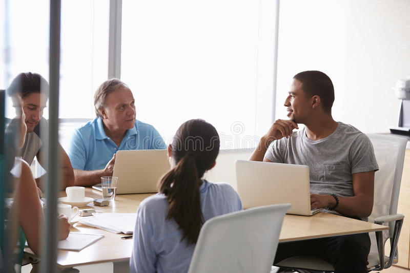 Cinque persone di affari che hanno riunione in sala del consiglio fotografia stock