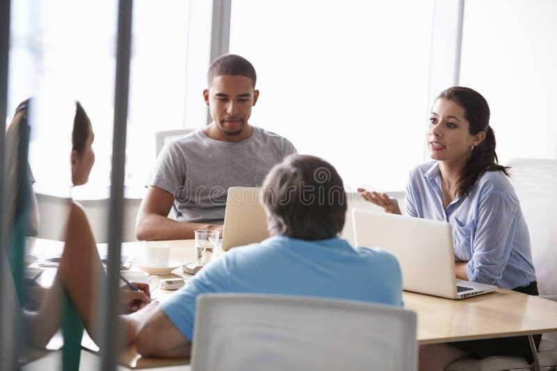Cinque persone di affari che hanno riunione in sala del consiglio fotografie stock libere da diritti