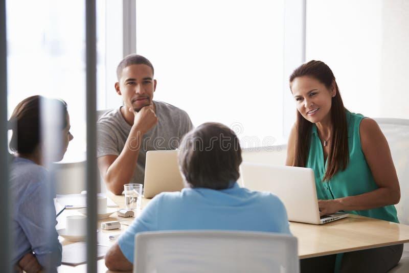Cinque persone di affari che hanno riunione in sala del consiglio immagini stock