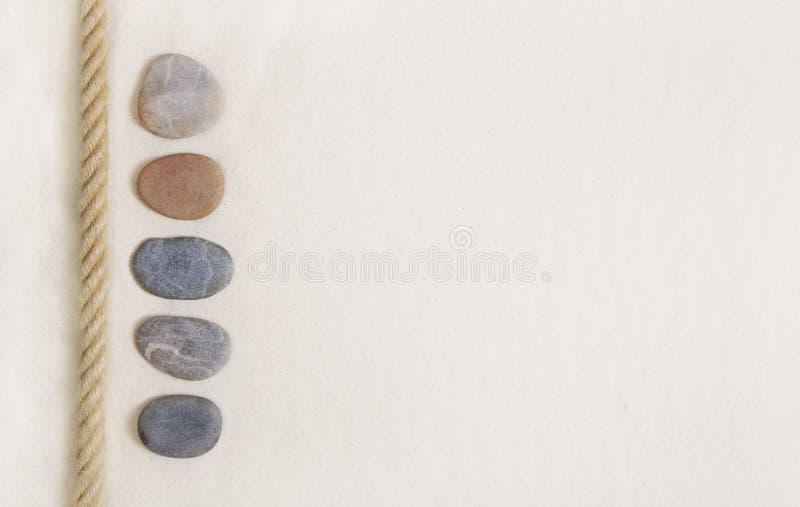 Cinque pietre nella sabbia beige Fondo per il raggiro di vacanza estiva immagini stock