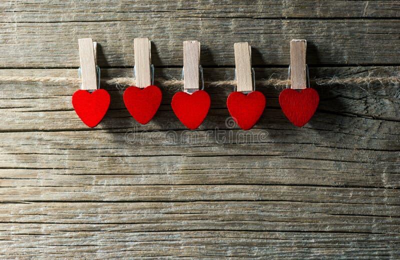 Cinque pioli con cuore rosso che appende sulla corda sul contesto di legno Giorno felice dei biglietti di S immagini stock