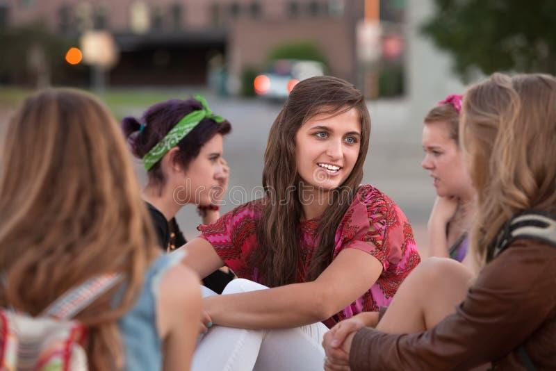 Cinque ragazze che si siedono all'esterno fotografia stock libera da diritti