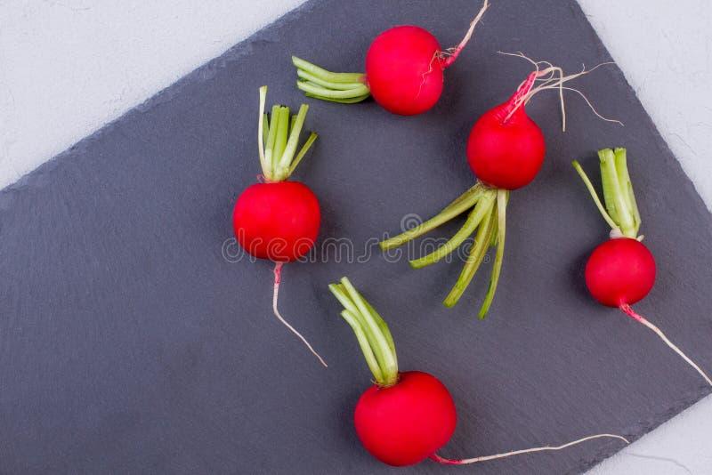 Cinque ravanelli sull'ardesia, vista superiore fotografia stock