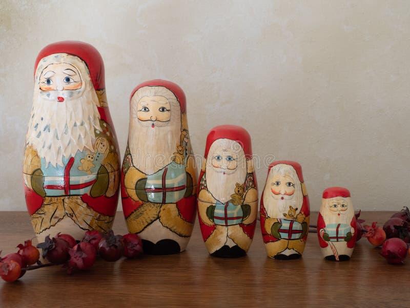 Cinque Santa Nesting Dolls di legno con le bacche che stanno in una fila immagine stock