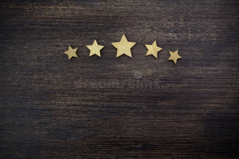 Cinque stelle dorate su fondo di legno, concetto di valutazione superiore fotografia stock libera da diritti