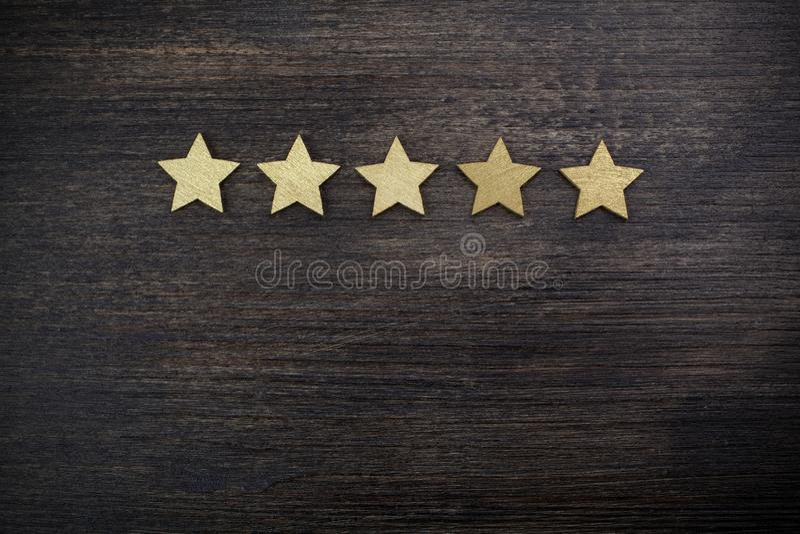 Cinque stelle dorate su fondo di legno, concetto di valutazione superiore immagini stock