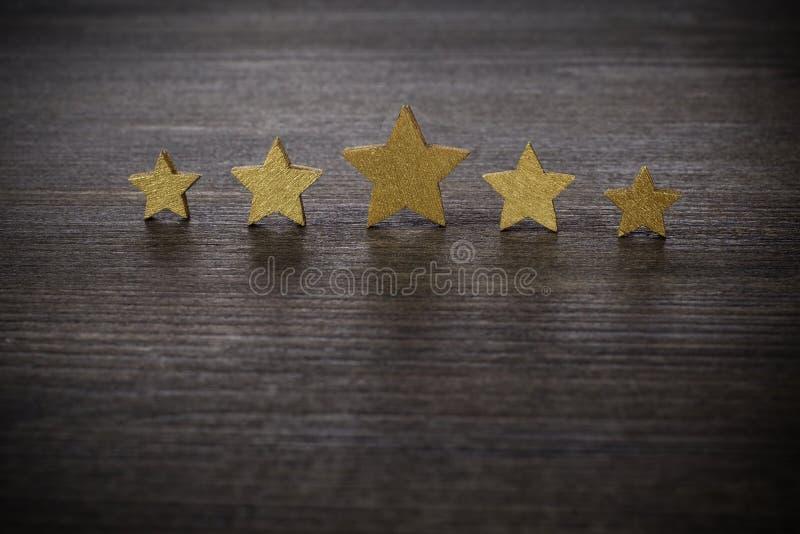Cinque stelle dorate su fondo di legno, concetto di valutazione superiore fotografia stock