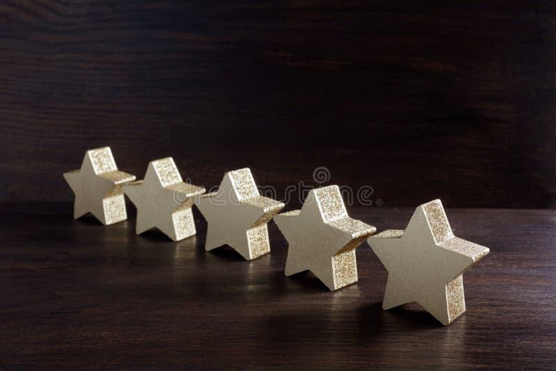 Cinque stelle dorate su fondo di legno scuro, concetto di valutazione superiore fotografie stock libere da diritti