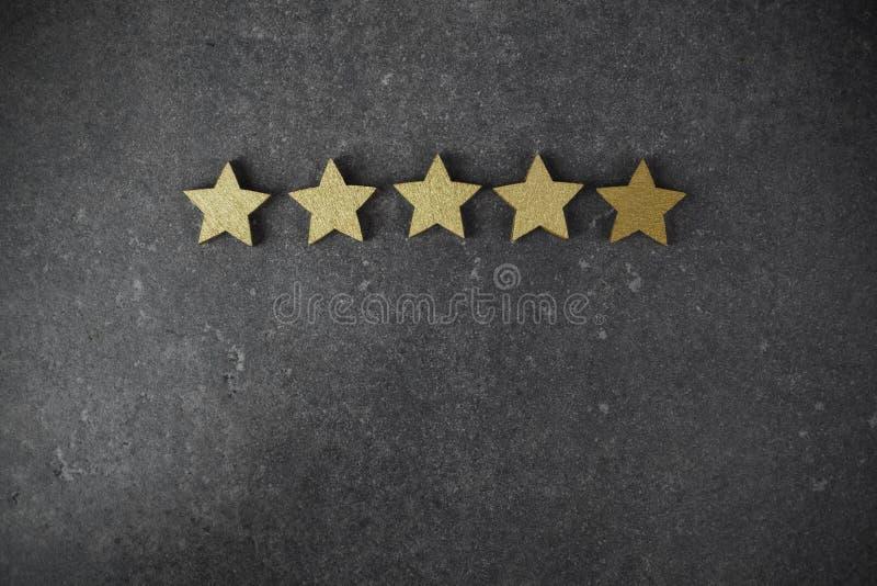 Cinque stelle dorate su fondo scuro, concetto di valutazione superiore fotografie stock libere da diritti