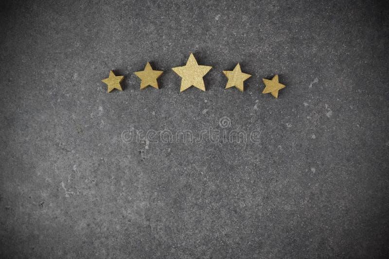 Cinque stelle dorate su fondo scuro, concetto di valutazione superiore immagini stock