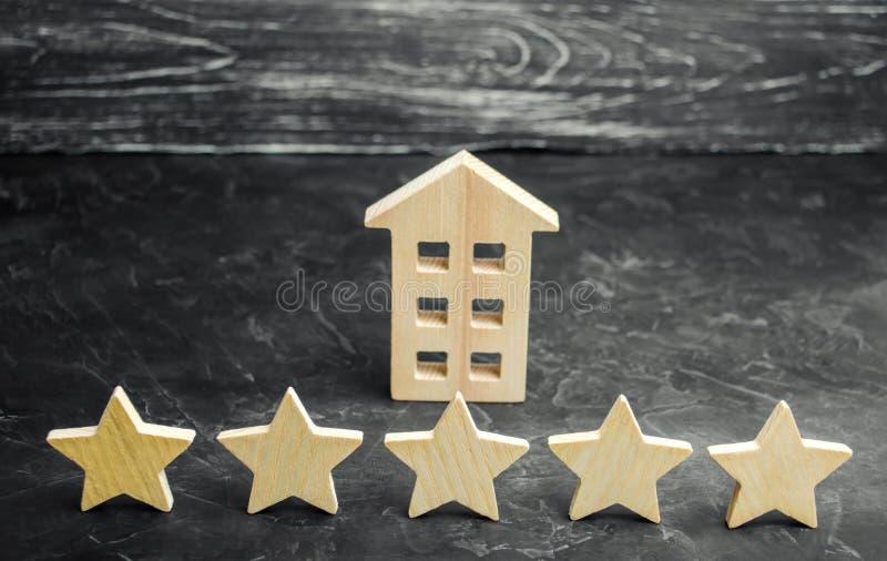 Cinque stelle e una casa di legno su un fondo concreto grigio Il concetto di migliore alloggio, classe di lusso degli appartament fotografia stock