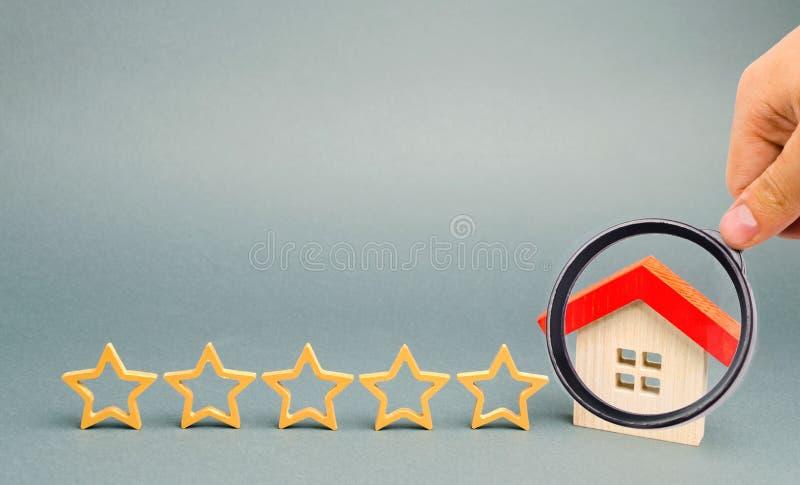 Cinque stelle e una casa di legno su un fondo grigio Il concetto di migliore alloggio, classe di lusso degli appartamenti VIP Il  fotografia stock