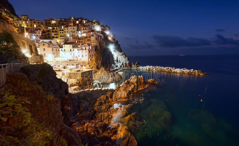 Cinque Terre seglar utmed kusten på natten royaltyfri foto