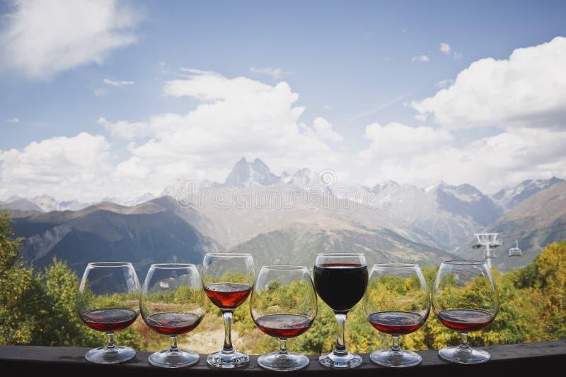 Cinque vetri del cognac e di due vetri di rosso e supporto del vino rosato contro il contesto di bei paesaggio della montagna e c immagini stock