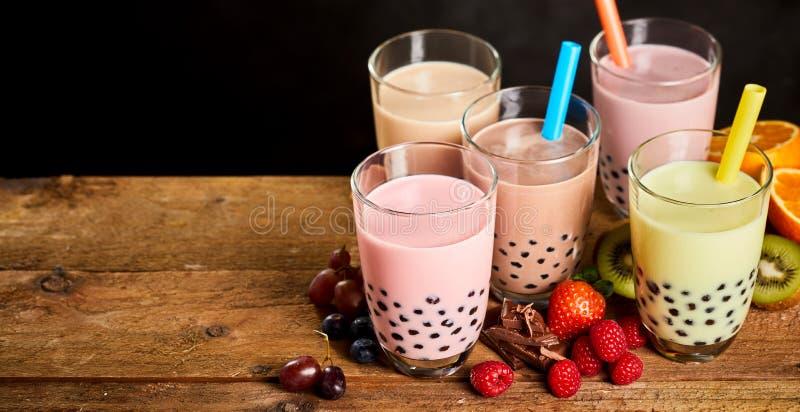 Cinque vetri del tè latteo della bolla con frutta fresca fotografie stock libere da diritti