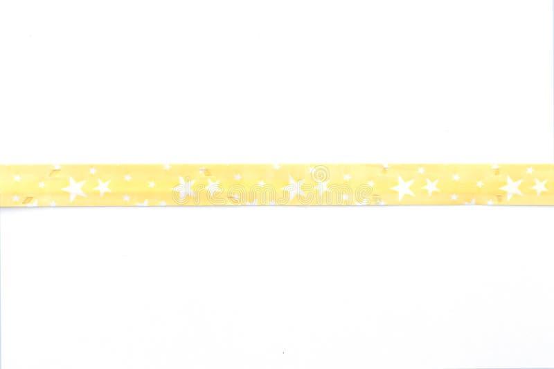 Cinta amarilla con el fondo blanco aislado arco imagen de archivo