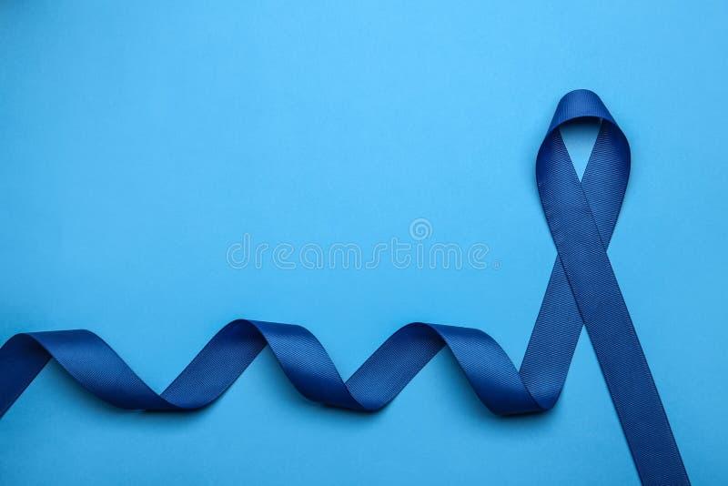 Cinta azul de la conciencia en el fondo del color, visión superior Símbolo de problemas sociales y médicos imágenes de archivo libres de regalías
