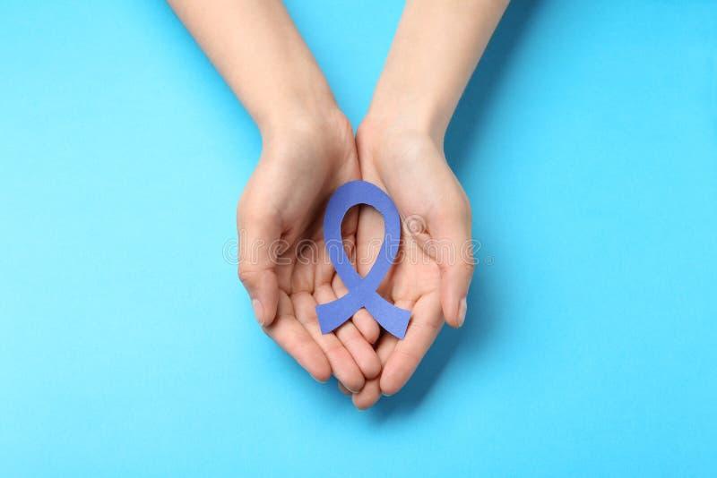 Cinta azul de la conciencia de la tenencia de la mujer en el fondo del color, visión superior Símbolo de social y de médico fotos de archivo