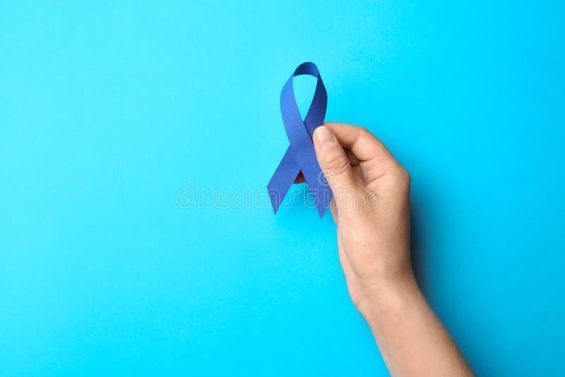 Cinta azul de la conciencia de la tenencia de la mujer en fondo del color Símbolo de problemas sociales y médicos fotografía de archivo