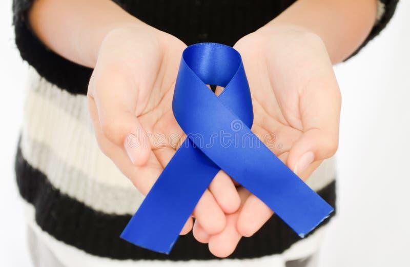 Cinta azul marino en la mano de la mujer, symboli de seda de la cinta de la tela de satén imagenes de archivo