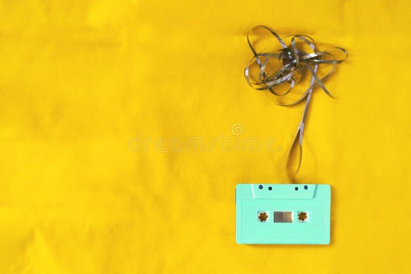 cinta de casete sobre fondo amarillo del material de la tela fotos de archivo libres de regalías