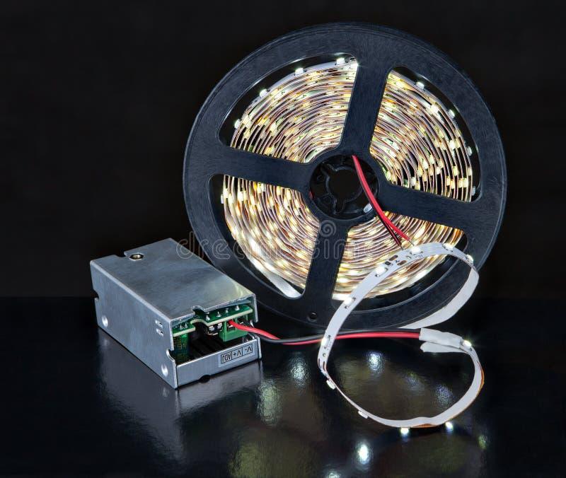 Cinta de la luz del brillo LED del primer en el carrete y el adaptador del voltaje fotos de archivo