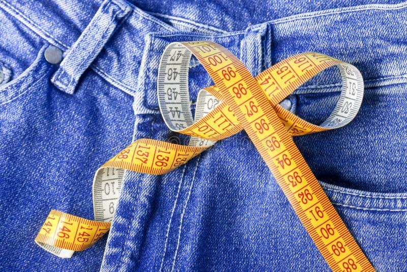 Cinta de medición contra el contexto de pantalones vaqueros fotos de archivo libres de regalías