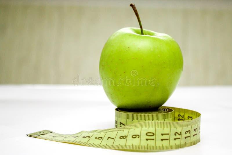 Cinta de medición y manzana verde foto de archivo